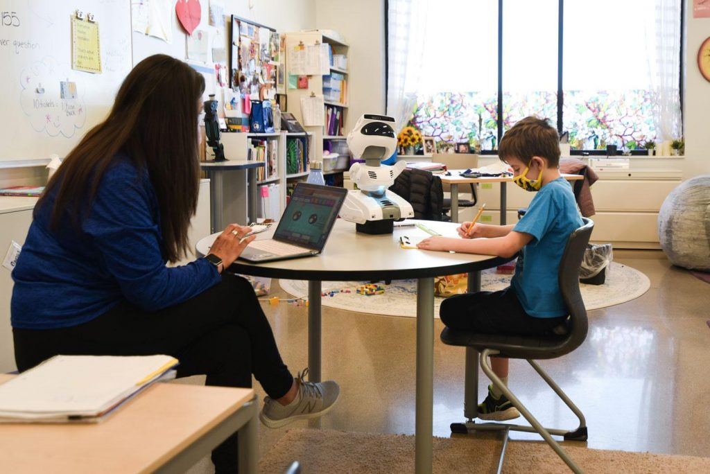 teacher and student working with Misty robot